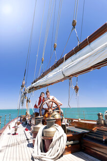 Happy mature couple at helm of a sailing ship - TOYF000820