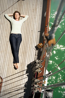 Relaxed mature woman lying on deck of a sailing ship - TOYF001038