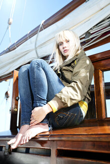 Young woman on a sailing ship sitting on a bench - TOYF000894