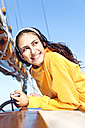 Smiling young woman on a sailing ship - TOYF000903