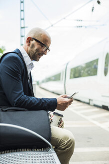 Businessman looking at cell phone on railway platform - UUF004406