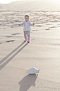 Baby girl standing on the beach looking at a shell - ZEF005256