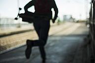 Blurred view of man with skateboard running on railway platform - UUF004416