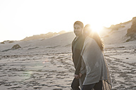 South Africa, Cape Town, young couple walking on the beach at sunset - ZEF005275