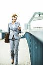 Businesswoman walking on bridge looking at cell phone - UUF004428