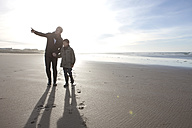 South Africa, Witsand, father and son walking on the beach at backlight - ZEF005293