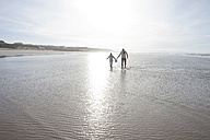 South Africa, Witsand, father and son wading through water at seafront - ZEF005301