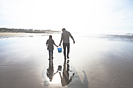 South Africa, Witsand, father and son walking on the beach at backlight - ZEF005304