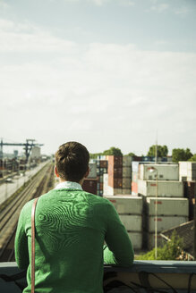 Man outdoors looking at freight yard - UUF004443