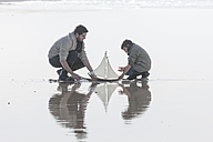 Father and son playing with toy sailing boat at seafront - ZEF005307
