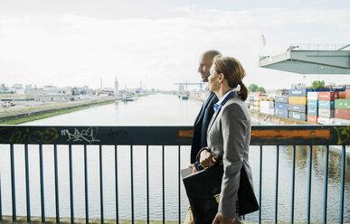 Businessman and businesswoman talking on bridge - UUF004450