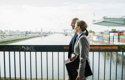 Businessman and businesswoman talking on bridge - UUF004450