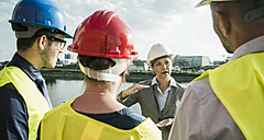 Businesswoman talking to people with safety helmets at riverside - UUF004474