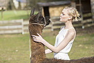 Woman face to face with llama on a paddock - TAMF000005