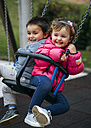 Spain, Little girl and boy sitting laughing on swing - MGOF000245