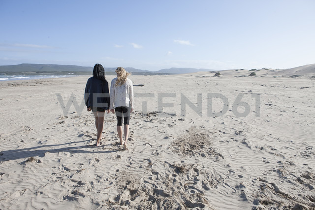 South Africa, Cape Town, back view of two young women walking on the beach - ZEF005201 - zerocreatives/Westend61