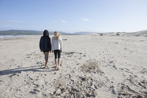 South Africa, Cape Town, back view of two young women walking on the beach - ZEF005201