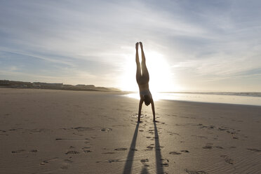 South Africa, Cape Town, silhouette of young woman doing handstand on the beach - ZEF005204