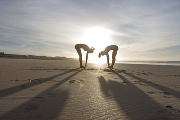 South Africa, Cape Town, two women doing stretching exercises on the beach - ZEF005208