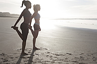 South Africa, Cape Town, two women doing stretching exercises on the beach - ZEF005435