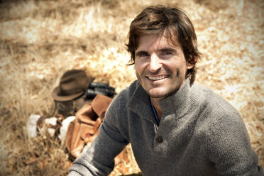 South Africa, portrait of smiling man sitting on a meadow - TOYF000970