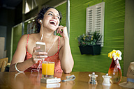 Portrait of happy woman hearing music with smartphone in a cafe - TOYF000973