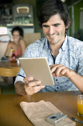 Portrait of smiling man using digital tablet in a cafe - TOYF001032