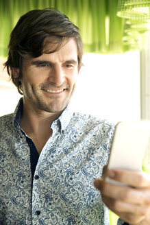 Portrait of smiling man using smartphone - TOYF000977