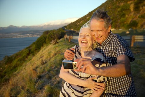 South Africa, happy senior couple taking a selfie by sunset - TOYF001005