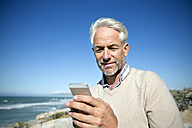South Africa, portrait of smiling man with smartphone - TOYF001011