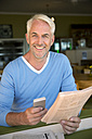Portrait of smiling man with smartphone reading a newspaper - TOYF001020