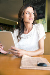 Portrait of woman with digital tablet in a cafe - TOYF001023