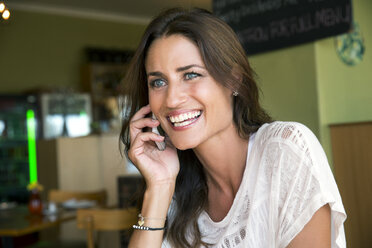 Portrait of smiling woman telephoning with smartphone in a cafe - TOYF001025