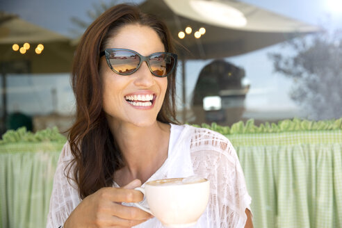 Portrait of smiling woman with cup of cappucino in front of a cafe - TOYF001028