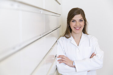Portrait of smiling female pharmacist leaning on drawer cabinet - FKF001060