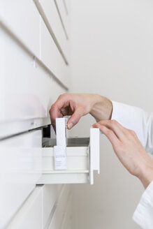 Hands of pharmacist taking drug from a drawer cabinet - FKF001064