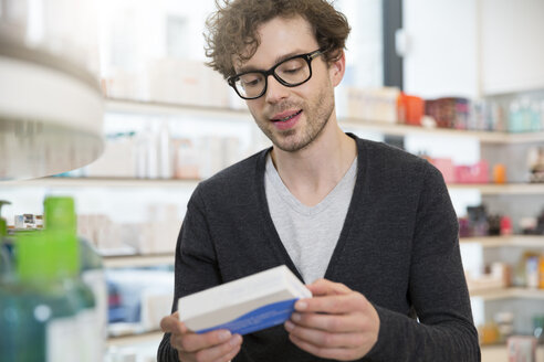 Portrait of man looking at product in a pharmacy - FKF001075