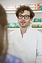 Portrait of pharmacist advising female customer - FKF001084