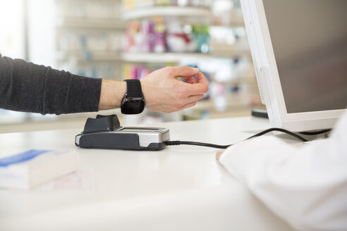 Customer paying cashless with smartwatch in a pharmacy - FKF001093