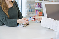 Portrait of female customer paying cashless in a pharmacy - FKF001119