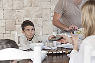 Family having lunch at dining room table with boy handing over digital tablet to mother - ZEF005377