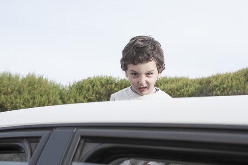 Boy looking through a sunroof of a car - ZEF005388