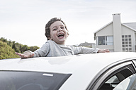 Happy boy looking through a sunroof of a car - ZEF005390