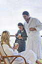 Family wearing bathrobes on patio of beach house - ZEF005393