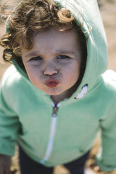 Portrait of little girl wearing hooded jacket pouting mouth - MGOF000255