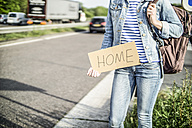Germany, female hitchhiker with sign 'home' waiting at roadside - RIBF000082