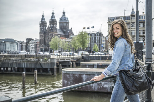 Netherlands, Amsterdam, female tourist in front of Amstel River - RIBF000073