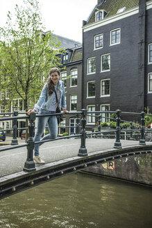 Netherlands, Amsterdam, female tourist standing on footbridge - RIBF000083