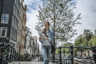 Netherlands, Amsterdam, female tourist with city map - RIBF000084