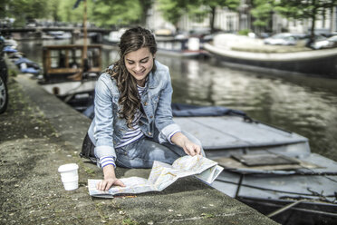 Netherlands, Amsterdam, female tourist having a rest looking at city map - RIBF000087